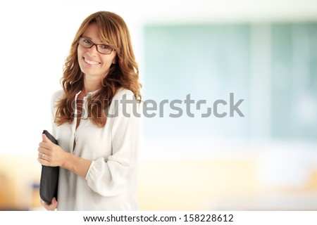 Smiling teacher standing at blackboard - stock photo