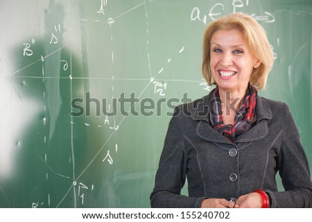 Smiling teacher standing in a classroom - stock photo