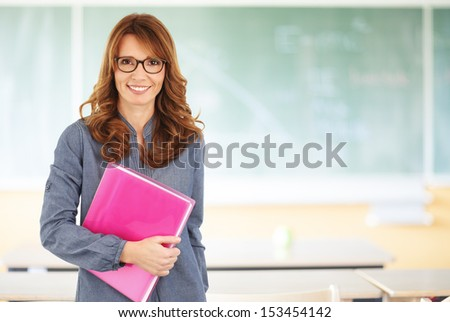 Smiling teacher standing in front of blackboard - stock photo