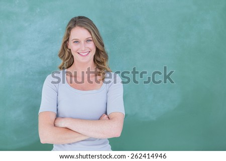 Smiling teacher standing in front of blackboard in classroom - stock photo