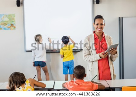 Smiling teacher using a tablet while pupils are working in classroom - stock photo