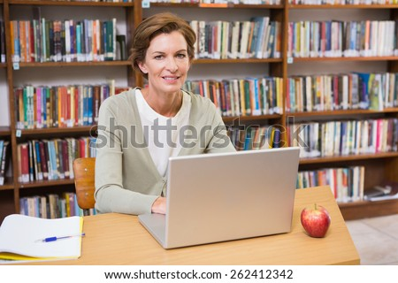 Smiling teacher using laptop at a desk at library at elementary school - stock photo