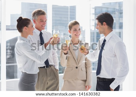 Smiling team of business people clinking their flutes of champagne in a bright office - stock photo