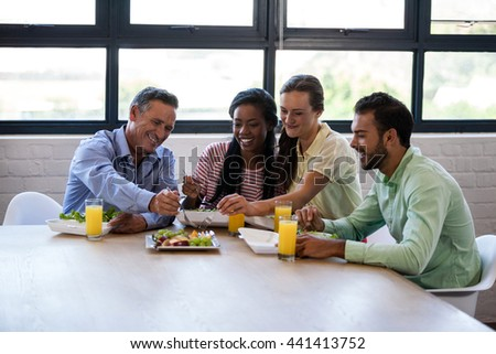 Smiling team of business people having lunch in modern studio - stock photo