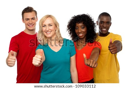 Smiling team of young people showing thumbs up isolated over white background - stock photo