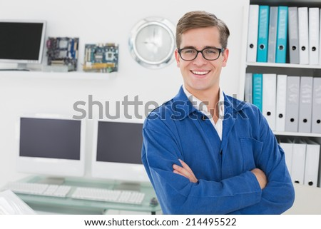 Smiling technician looking at camera in his office - stock photo