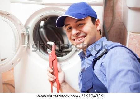 Smiling technician repairing a washing machine - stock photo