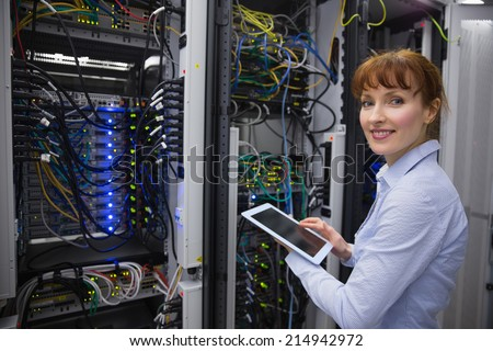 Smiling technician using tablet pc while analysing server in large data center - stock photo