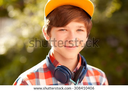 Smiling teen boy 14-16 year old posing outdoors. Looking at camera.  - stock photo
