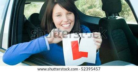 Smiling teen girl sitting in her car tearing a L-sign after having her driver's licence - stock photo