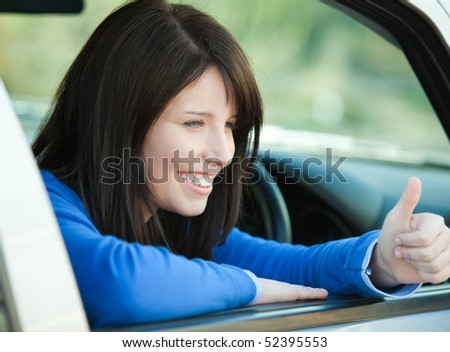 Smiling teen girl with a thumb up sitting in her car after having her driver's licence - stock photo
