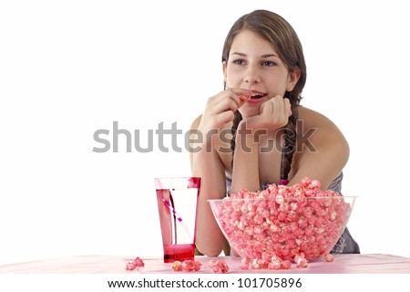 Smiling teen girl with long braids leans elbows on table and eats popcorn. Large bowl of pink popcorn and tall glass with straw on table in foreground. Horizontal, isolated on white with copy space.