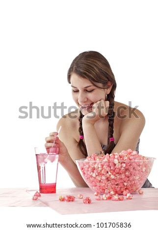 Smiling teen girl with long brown braids enjoys snack. Large bowl of pink popcorn and tall glass with straw are on table in foreground. Vertical, isolated on white with copy space.