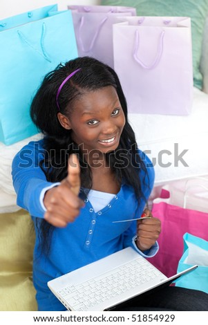 Smiling teen girl with thumb up shopping on-line in the living-room - stock photo