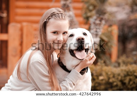 Smiling teen girl 14-16 year old holding labrador dog outdoors. Looking at camera. Happiness. Friendship.