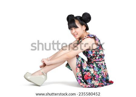 Smiling teenage asian girl sitting on the floor, Isolated over white - stock photo