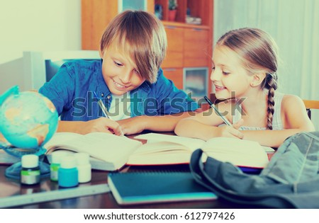 Smiling teenage boy and cute little girl studying with books indoors