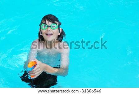 Smiling teenage boy in the pool pointing an orange water gun.