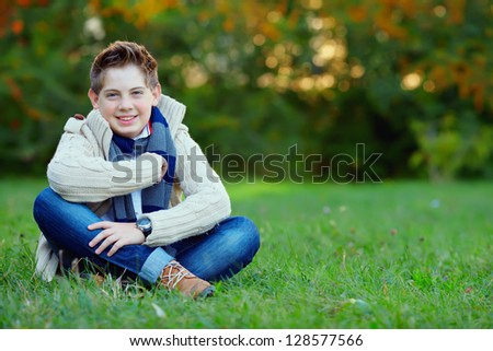 smiling teenage boy on green lawn - stock photo