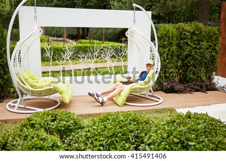 Smiling teenage boy sits in white swing hanging on chain in summer park.