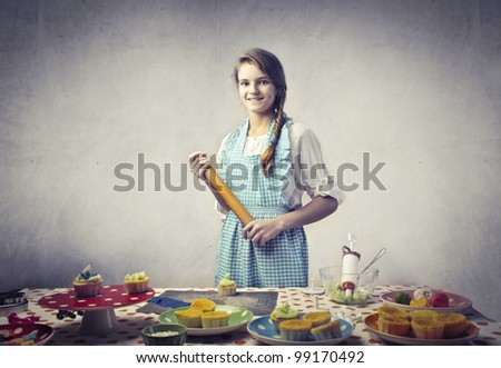 Smiling teenage cook showing her food creations - stock photo