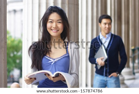 Smiling teenage female student outdoors with a boy at the background - stock photo