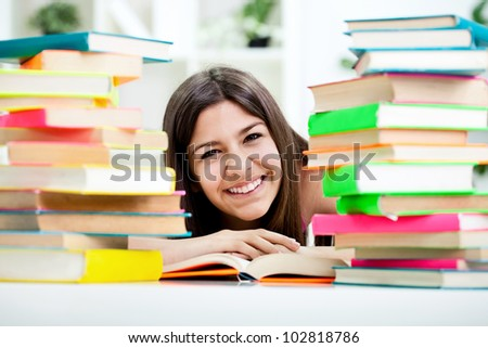 Smiling teenage girl between stack of book , concept - education - stock photo