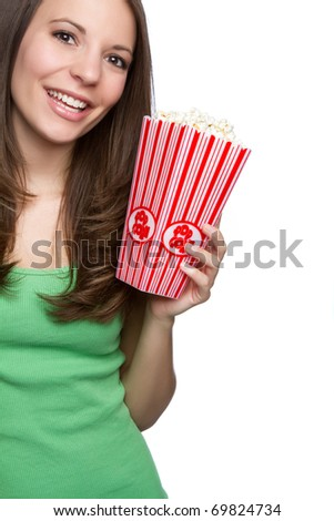Smiling teenage girl eating popcorn - stock photo