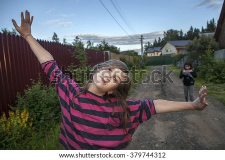 smiling teenage girl in a red striped shirt standing on the street between the houses, her arms up to the sky. - stock photo