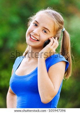 Smiling teenage girl in blue dress talking on cell phone, of green summer park. - stock photo