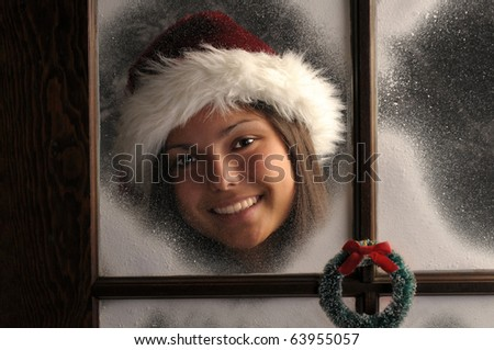 Smiling Teenage girl in window covered with frost wearing a Santa Hat.