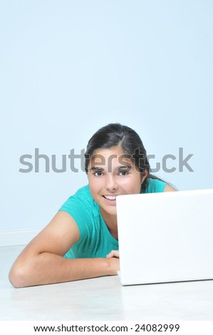 Smiling teenage girl laying on the floor with laptop computer