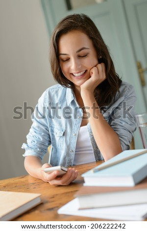 Smiling teenage girl looking at mobile phone studying at home - stock photo