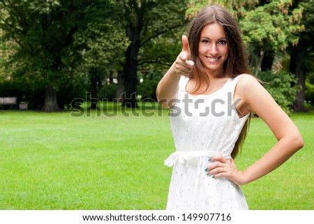 Smiling teenage girl picks up big thumbs up, against green of summer park.