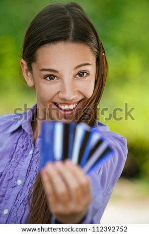 Smiling teenage girl shows credit card, against green of summer park. - stock photo
