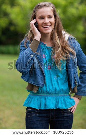 Smiling teenage girl talking with her mobile phone while standing in the countryside