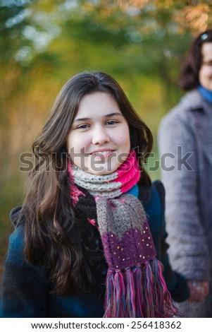 Smiling teenage girl with her mother walking outdoors. - stock photo