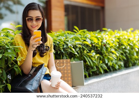 Smiling teenage girl with phone texting outdoors - stock photo