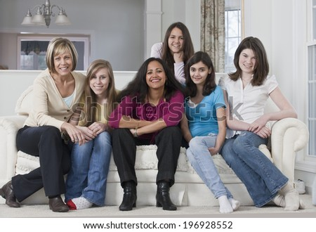 Smiling teenage girls with their mothers sitting on a white sofa at home