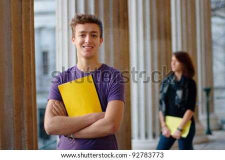 Smiling teenage student outdoors with a girl at the background - stock photo