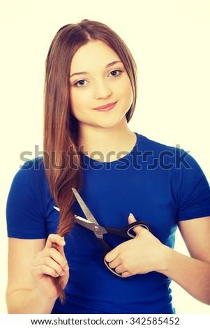Smiling teenage woman cutting her hair. - stock photo