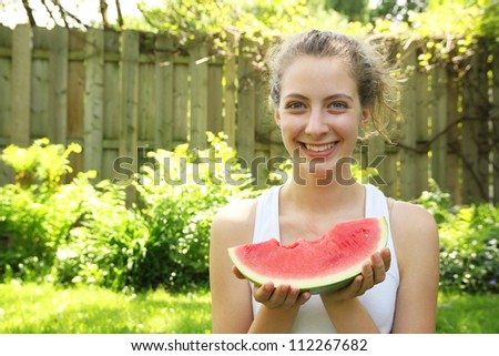 Smiling teenager eating a watermelon in a sunny backyard