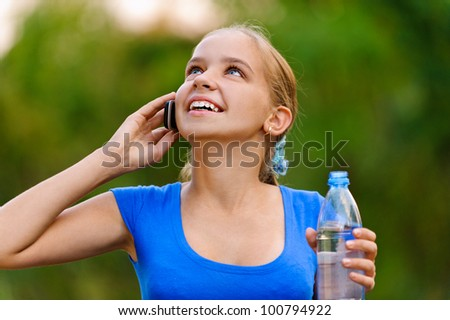 Smiling teenager girl in blue dress holding water bottle and talking on cell phone in green summer park.