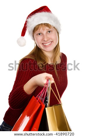 Smiling teenager girl in christmas hat with shopping bags