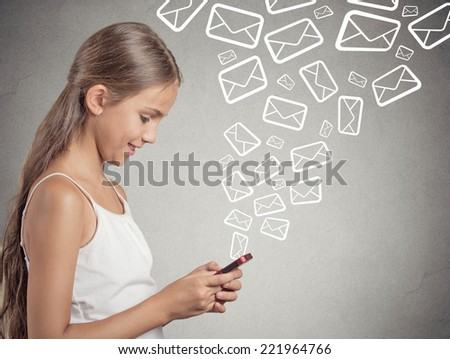 smiling teenager girl standing holding smart phone texting, sending message, email icons coming out of mobile phone isolated grey wall background. telecommunications, internet, 4g data plan concept - stock photo