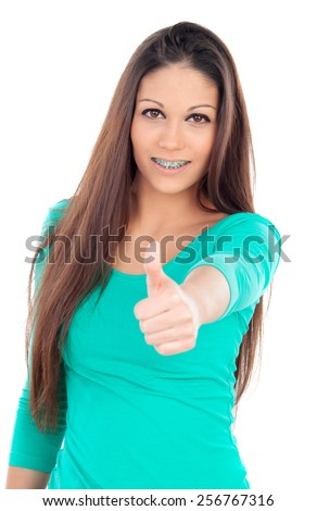 Smiling teenager girl with brackets saying Ok isolated on a white background - stock photo