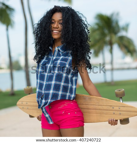Smiling teenager holding long board in South Pointe Park. South Beach Miami, Florida.