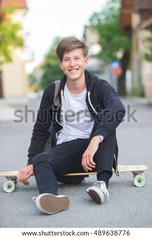 Smiling teenager sitting on his longboard wearing a backpack.