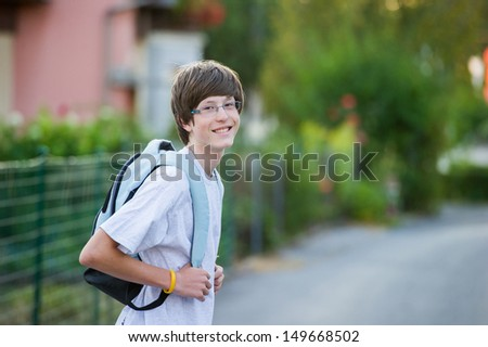 Smiling teenager wearing a school bag in a suburban setting - stock photo