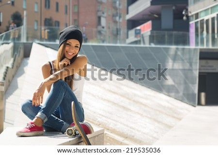 Smiling teenager with skateboard portrait outdoors.  - stock photo